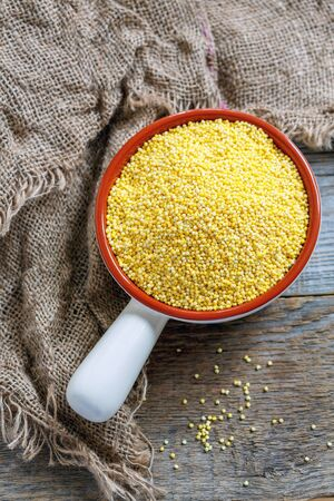 Raw millet in ceramic bowl and old sacking on a wooden table. Stock Photo