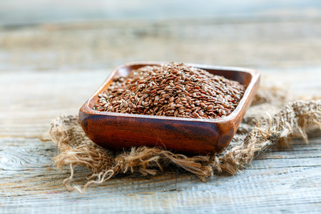 Flax seeds in a wooden bowl on old table. Stock Photo