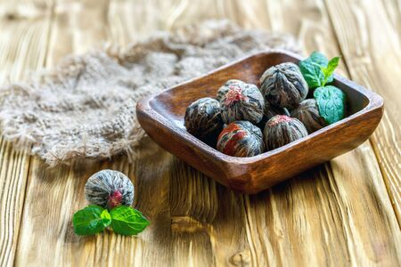 Chinese flowering tea balls in bowl on a wooden table with sacking,selective focus.