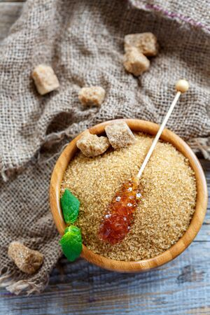 Stick with crystal brown sugar in a bowl and old sacking on a wooden table, selective focus. Stock Photo