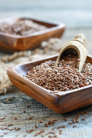 linseed: Bowl with brown flax and scoop on an old wooden table, selective focus. Stock Photo