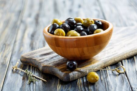 Green and black olives in a bowl on old wooden table. Stock Photo