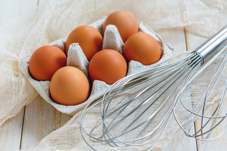 Brown eggs with stainless steel whisk on a white wooden table.