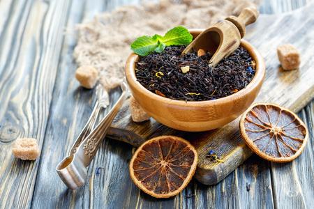 Zwarte thee in een kom en suiker tang op de oude houten tafel, selectieve focus. Stockfoto