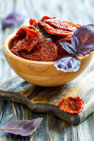 Bowl with sun-dried tomatoes and purple basil on wooden table, selective focus.