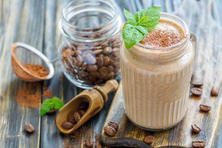 Coffee smoothie in a glass jar on the kitchen wooden table, selective focus.