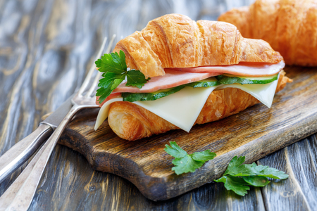 Croissant with ham, cheese, cucumber and parsley on an old wooden table.