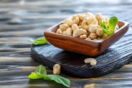 Cashew nuts and fresh mint in bowl on old table, selective focus.