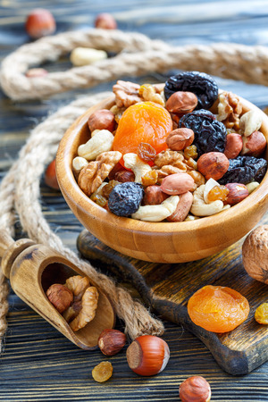 Mixture of nuts and dried fruit in a wooden bowl, selective focus. 免版税图像