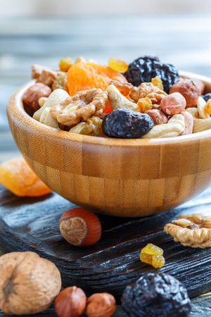 Bowl with nuts and dried fruits on dark wooden stand, selective focus.