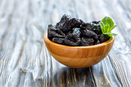 Dried black plums in a bowl on old wooden table, selective focus. Standard-Bild
