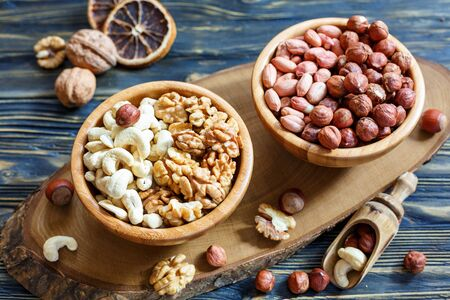 Peanuts, hazelnuts, cashews and walnuts in bowls on a wooden table.