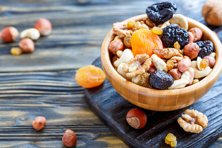 Bowl with a mixture of dried fruit and nuts on an old kitchen table, selective focus.