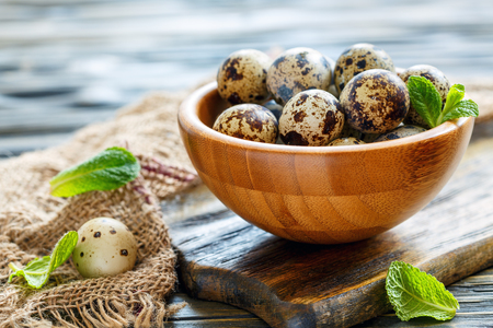 Quail eggs in bowl on a wooden table with old burlap, selective focus.