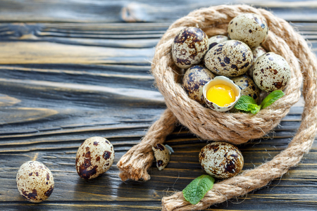 Quail eggs and yolk in the shell on the old wooden table, selective focus. Zdjęcie Seryjne