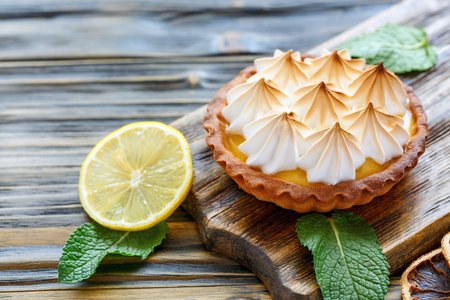Tartlet with Italian meringue and lemon cream on a wooden stand, selective focus. Stock Photo