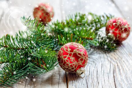 Christmas red balls with gold ornaments and spruce branch on old wooden table. Stock Photo