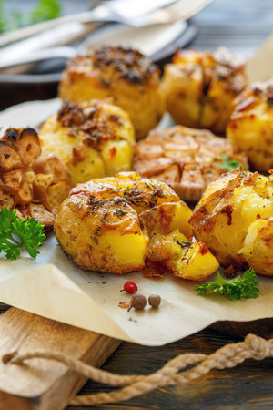 Potatoes baked in their skins with spices and green parsley on a sheet of parchment, selective focus. Stock Photo
