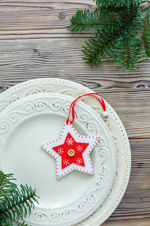 Vintage porcelain plates with Christmas decoration on old wooden background.