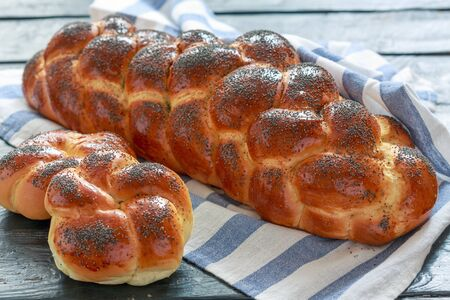 Fresh challah bread with poppy seeds on a linen towel, selective focus. 版權商用圖片