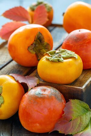Juicy persimmons, colorful autumn leaves on a old wooden box, selective focus.