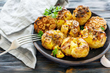 Baked potatoes in skin with spices, olive oil and garlic on a wooden dish, selective focus. Stock Photo