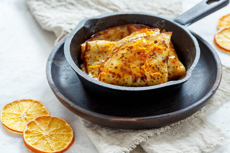 Traditional French crepe Suzette with orange sauce in a cast iron pan. 스톡 콘텐츠