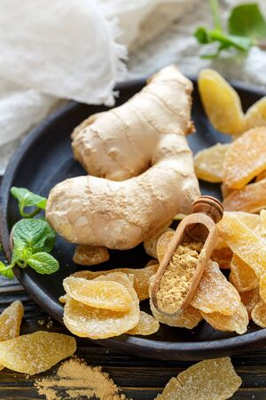 Ginger root, spicy ginger candied fruit and scoop with ground ginger on wooden dish, selective focus.