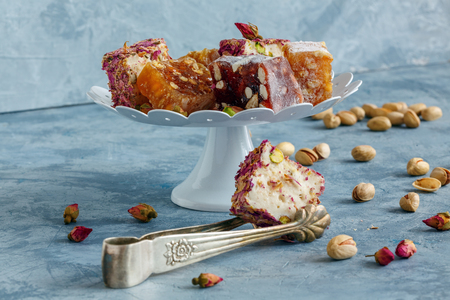 Turkish delight with pistachio and rose petals on a white stand and tweezers for sweets. 免版税图像