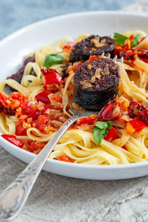 Fork in a plate with Italian pasta, tomato sauce, red pepper and blood sausages. Stockfoto