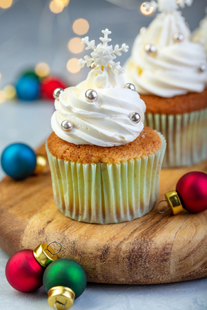 Vanilla cupcakes with Christmas decor and colorful balls on a wooden serving board on a blurred background of lights, selective focus. Stock Photo