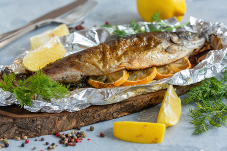 Trout with lemon, greens, pepper mixture baked in foil, selective focus. 免版税图像