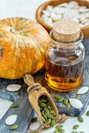Bottle with pumpkin oil, ripe pumpkin, wooden scoop with pumpkin seeds on textured white background, selective focus. 스톡 콘텐츠