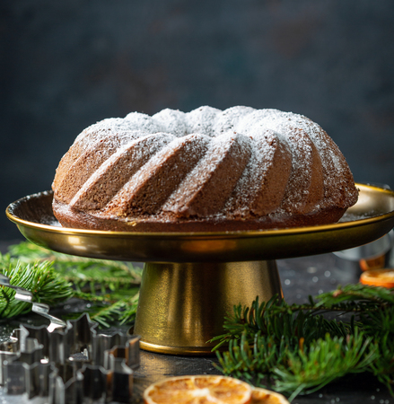 Homemade gingerbread cake and cookie molds on a dark background with fir branches, selective focus. 스톡 콘텐츠