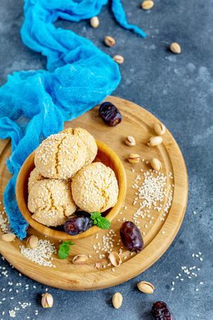 Wooden bowl with Moroccan cookies with white sesame seeds on textured dark background. Top view.
