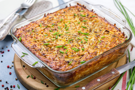 Glass pan with traditional potato kugel on wooden serving board, selective focus. Imagens