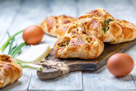 Puffs mit Spinat, Eiern, Frühlingszwiebeln und Käse auf einem hölzernen Servierbrett, selektiver Fokus.