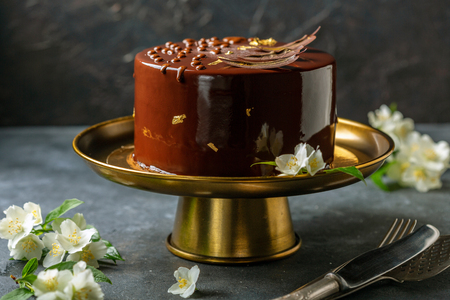 Chocolate mousse cake in mirror glaze on a bronze stand, on a dark textured background, selective focus. Stock Photo