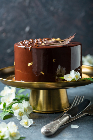 Modern mousse cake with chocolate decor and food gold on a bronze stand, on a dark textured background, selective focus.