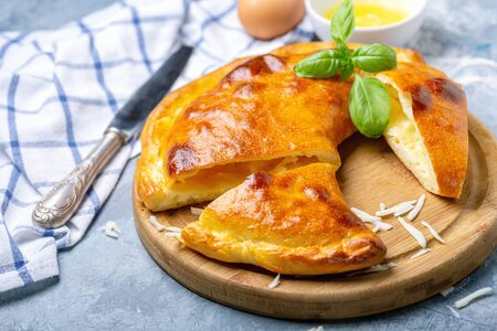 Traditional closed pie with cheese and egg in the shape of a crescent cut into pieces on a wooden serving board, selective focus. Stockfoto - 124997321