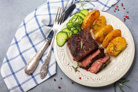 Roast entrecote, baked potatoes, rosemary and pink pepper on a plate, gray textured background. Top view.