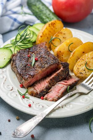 Plate with fried entrecote, baked potatoes, rosemary and pink pepper on a gray textured table, selective focus.