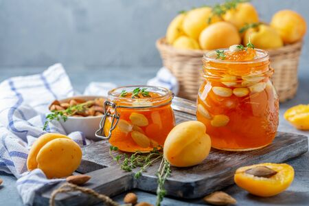 Homemade apricot jam with almonds and thyme in small glass jars on a wooden serving board, selective focus.