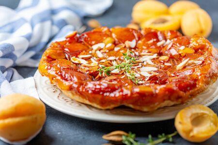 Hausgemachte Tarte Tatin Pie mit Aprikosen und Mandeln auf einem strukturierten grauen Tisch, selektiver Fokus.