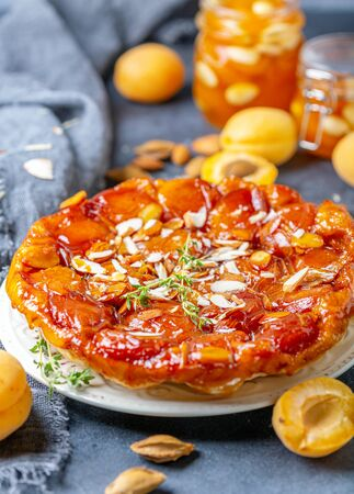 Traditional inverted pie with apricots and thyme on a dark textured table, selective focus. Archivio Fotografico