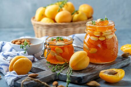 Homemade apricot jam with almonds and thyme in small glass jars on a wooden serving board, selective focus. Zdjęcie Seryjne