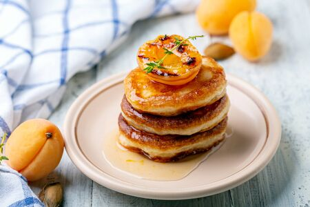 Thick pancakes or fritters are served with apricot jam and caramelized apricot on a ceramic plate, selective focus. White wooden background.