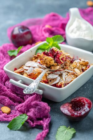 Plum crumble with oatmeal, almond flakes and thick homemade yogurt in a bowl on a dark textured background, selective focus.