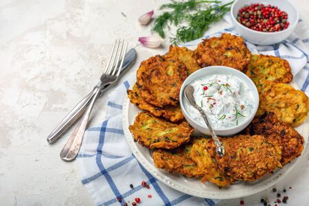 Zucchini fritters with sauce on a white plate on a textured white background with copy of space. Zdjęcie Seryjne