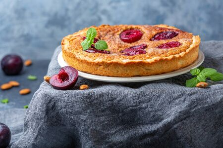 Plum pie with almond cream on the table with dark homespun cloth, selective focus.